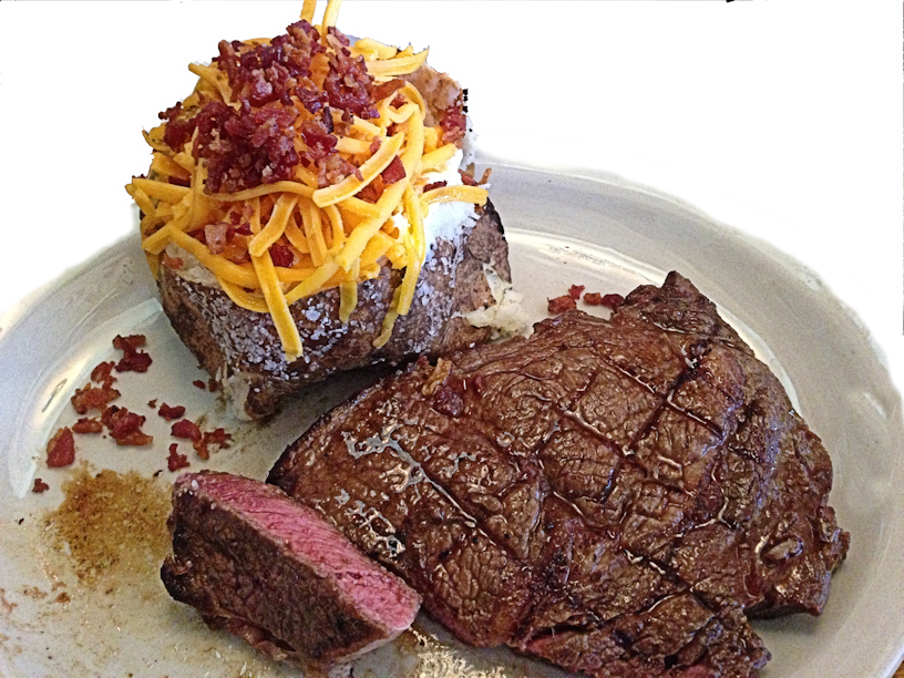Grilled rib-eye steak with baked potato